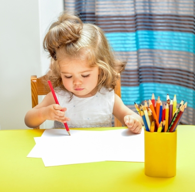 Little girl draws pencils. Interior of the room.
